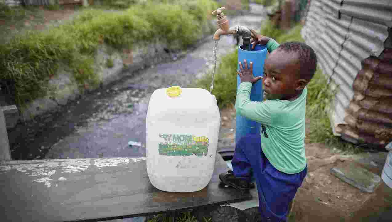 This picture shows a South African boy collecting his water for the entire week.